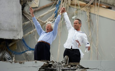 Two men celebrate after being pulled out from a destroyed building in Christchurch February 23, 2011.      REUTERS/Christchurch Press/John Kirk-Anderson