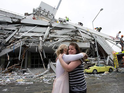 """Two women hug each other in front of a collapsed building in central Christchurch February 22, 2011. A strong quake hit New Zealand's second-biggest city of Christchurch on Tuesday for the second time in five months, toppling buildings, causing """"multiple fatalities,"""" trapping people beneath rubble and sparking fires. (REUTERS/Christchurch Press/John Kirk-Anderson)"""