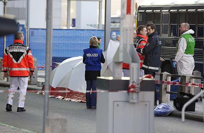 Emergency services, police and forensic experts stand next to an U.S. Army bus, following a shooting incident in front of Frankfurt airport  March 2, 2011.  REUTERS/Sascha Rheker