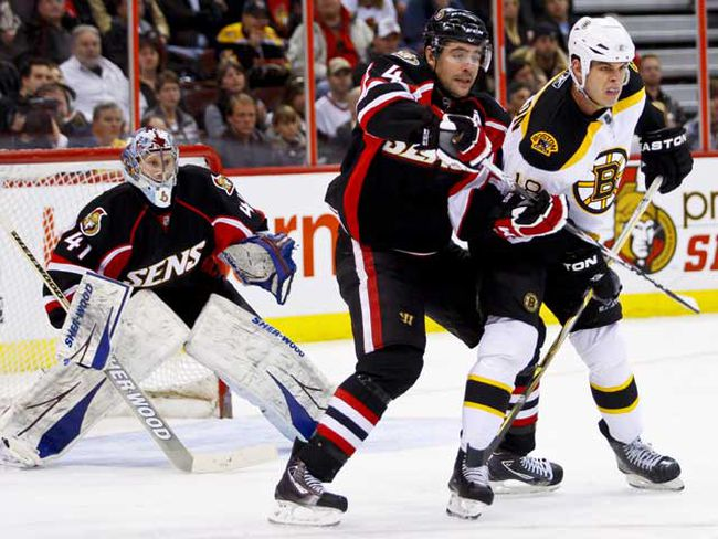 Ottawa Senators Chris Phillips battles with Boston Bruins Nathan Horton in front of Sens goaltender Craig Anderson during second period action at Scotiabank Place on Tuesday. (ERROL MCGIHON/QMI Agency)