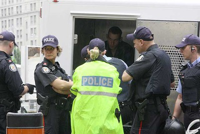 A protester sits in the back of a police wagon after being arrested near Toronto's Union Station. (STAN BEHAL, Toronto Sun)