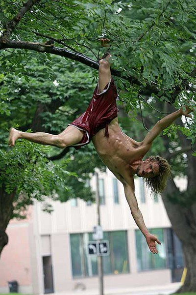 Kirk Warrington, 26, of Cambridge, spent the night entertaining the crowd at the tent city at Allan Gardens with oil wresting and other antics like tree climbing. (MICHAEL PEAKE/Toronto Sun)