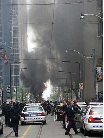Smoke billows in downtown Toronto Saturday after protesters set a police car on fire. (DAVE THOMAS/QMI Agency)