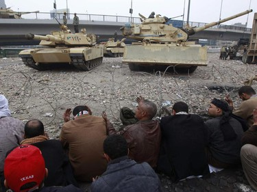 Opposition demonstrators pray in front of army tanks alongside the Egyptian Museum on the front line near Tahrir Square in Cairo February 5, 2011. The army brought the tanks in order to bring down the barricades but the protesters stood in defiance and the tanks stopped. (REUTERS/Yannis Behrakis)