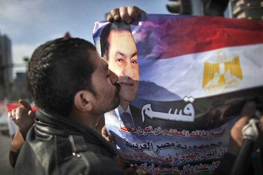 A supporter of Egyptian President Hosni Mubarak kisses his picture during a pro-regime demonstration in Cairo on February 2, 2011. Partisans of Mubarak stormed a crowded anti-regime rally in central Cairo, sparking pandemonium in which at least 500 people were hurt and one killed, witnesses said. AFP PHOTO/MARCO LONGARI