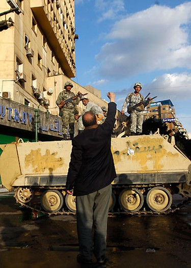 A protester raises his fist in front of an army Armoured Personnel Carrier (APC) in Cairo's Tahrir Square January 31, 2011. REUTERS/Yannis Behrakis