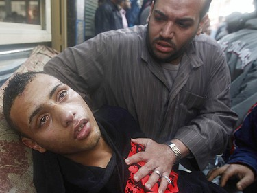A protester attends to an injured man during clashes in Cairo January 28, 2011. (Reuters)
