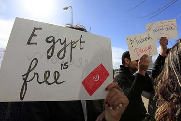 """People hold signs during a protest in front of Egypt's embassy in Tunis January 28, 2011. The protest was held to demand the end of Egypt's President Hosni Mubarak's 30-year rule as part of a wave of unrest gripping the Middle East. The sign in centre reads: """"Out Mubarak"""".      REUTERS/Zohra Bensemra"""