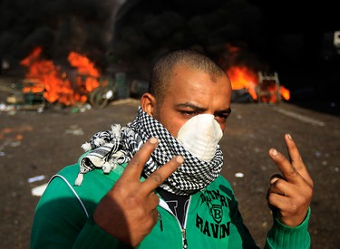 A protester gestures in front of a burning barricade during a demonstration in Cairo January 28, 2011.  REUTERS/Goran Tomasevic
