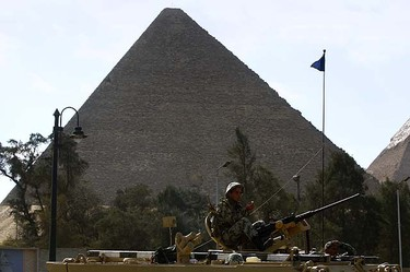 A soldiers mans a machine gun atop an Armoured Personnel Carrier (APC) near the Pyramids in Cairo January 31, 2011. Protesters intensified their campaign on Monday to force Egypt's President Hosni Mubarak to quit as world leaders struggled to find a solution to a crisis that has torn up the Middle East political map. REUTERS/Yannis Behrakis