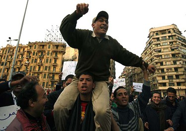 A protester carries a soldier on his shoulders as they chant anti-government slogans during a demonstration in Cairo January 30, 2011.  REUTERS/Asmaa Waguih