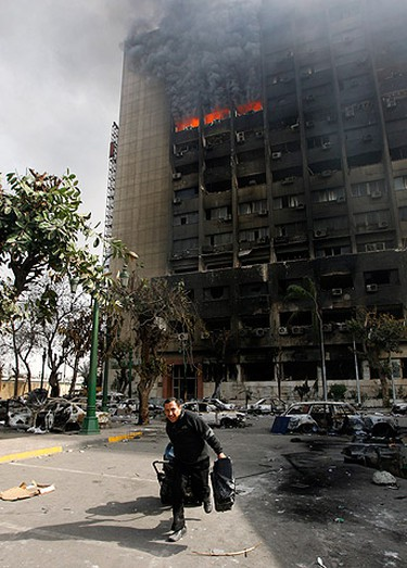 A looter runs away from the burning building of the ruling National Democratic party in Cairo on January 29, 2011. (REUTERS/Yannis Behrakis)