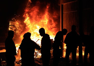 Protesters stand in front of the burning entrance of the ruling National Democratic Party building in Cairo on January 28, 2011. (REUTERS/Goran Tomasevic)