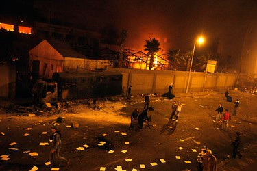 Protesters stand near the burning headquarters of the ruling National Democratic Party in Cairo January 28, 2011. REUTERS/Asma Waguih