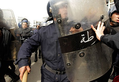 An anti-government protester pushes riot police during a demonstration in Algiers, Algeria on Feb. 19, 2011. (REUTERS)