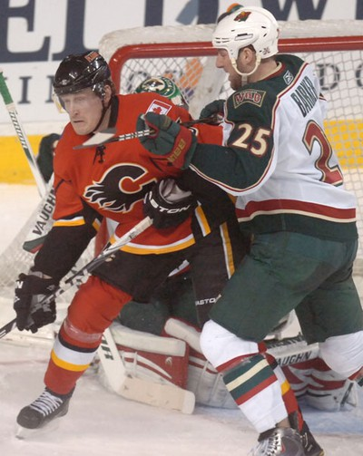 Tim Jackman from the Calgary Flames goes up against goalie Cam Barker from the Minnesota Wild in NHL action at the Scotiabank Saddledome in downtown Calgary, Alberta. on January 19, 2011. STUART DRYDEN/QMI AGENCY