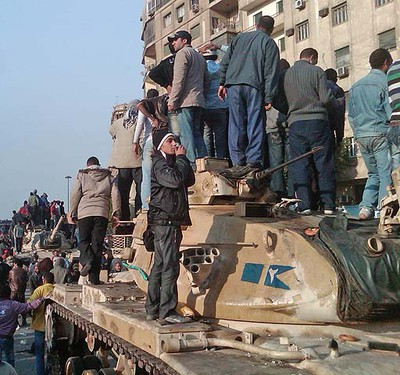 Bystanders stand on tanks to look over rock battles between pro and anti Mubarak forces in Cairo Wednesday February 2, 2011. (RICHARD LATENDRESSE/QMI AGENCY)