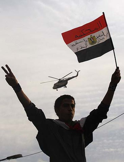 A protester holds an Egyptian flag as an army helicopter flies overhead thousands of anti-government protesters gathered for a sixth day at Tahrir square in Cairo January 30, 2011. Egyptian air force fighter planes buzzed low over Cairo on Sunday, helicopters hovered above and extra troop trucks appeared in a central square where protesters were demanding an end to President Hosni Mubarak's rule.  REUTERS/Yannis Behrakis
