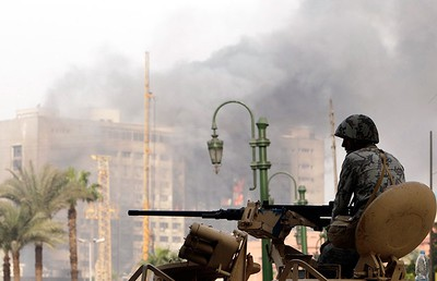 An Egyptian army soldier sits atop of an armoured personnel carrier in front of smoke going from the headquarters of the ruling National Democratic Party (NDP) in Cairo after wide-spread protests early January 29, 2011. (REUTERS/Amr Abdallah Dalsh)