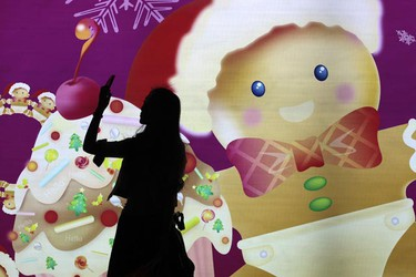 A woman takes pictures of Christmas decorations in a shopping mall in Hong Kong Nov. 24,2010. (Tyrone Siu/REUTERS)