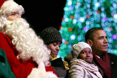 U.S. President Barack Obama looks up at the stage as his daughter Sasha looks at Santa Claus during the National Christmas Tree lighting ceremony on the Ellipse in Washington Dec. 9, 2010. Also pictured is daughter Malia (second left). (Kevin Lamarque/REUTERS)