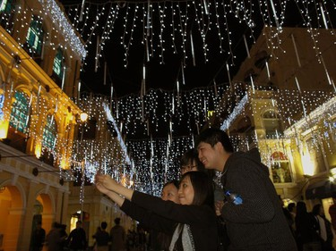 Visitors to Largo do Senado, the centre square in Macau, take a photo of themselves among Christmas decorations Dec. 20, 2010, the day marking the 11th anniversary of the enclave's handover to Chinese rule from Portugal. (Bobby Yip/REUTERS)