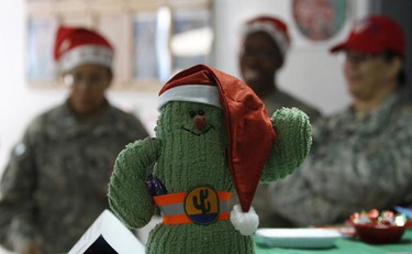 A Christmas cactus ornament is seen in front of U.S. military personnel from 103rd Sustainment Command (Expeditionary) as they attend Christmas festivities at a military base in Balad, 80 km north of Baghdad Dec. 24, 2010. (Saad Shalash/REUTERS)