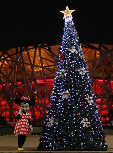 A staff from the Olympic Green area dressed as Disney's Minnie Mouse walks by one of many Christmas trees outside the National Stadium, also known as the Bird's Nest, on Christmas eve in Beijing Dec. 24, 2010. (Christina Hu/REUTERS)