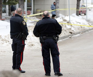 Winnipeg Police officers hold a position at Elgin Avenue and Ellen Street Saturday, Feb. 5, 2011 after two males were fatally shot approximately 2:30 a.m. (BRIAN DONOGH/Winnipeg Sun)