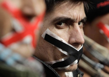 Immigrants and asylum seekers, with their mouths taped, protest to demand for asylum in central Athens February 1, 2011. An estimated half a million illegal immigrants and asylum seekers live in the Mediterranean state of about 11 million inhabitants, many of them in Athens, and an increasing share of those trying to reach the EU come in through Greece.  REUTERS/John Kolesidis