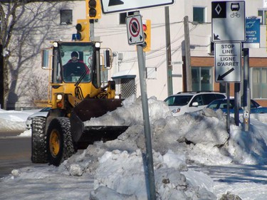 A front-end loader clears snow from a high bank on St. Anne's Road Tuesday, Feb. 1, 2011. The city typically clears snow away from high snowbanks near intersections, crosswalks and other public places where they can become hazards. (PAUL TURENNE/Winnipeg Sun)