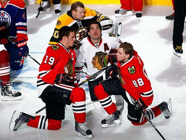 Chicago Blackhawk teammates Jonathan Toews of Team Nicklas Lidstrom, Patrick Sharp of Team Eric Staal and Patrick Kane of Team Nicklas Lidstrom kneel on the ice during the NHL All-Star hockey skills competition in Raleigh, N.C., Jan. 29, 2011. (REUTERS/Shaun Best)