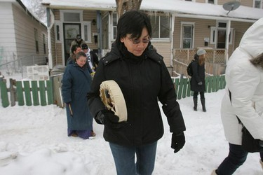 Friends and family of Nathaniel Thorassie, including Nathaniel's mother Mclaine Flett (middle), drummed, prayed and smudged Jan. 27, 2011 near the scene where the six-year-old boy was lost in the cold waters of the Red River in December. (MARCEL CRETAIN/Winnipeg Sun)