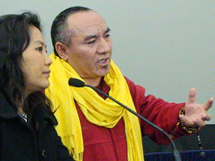 Tibetan monk Nawang Choedon, with the help of an interpreter, voices his anger after funding cuts to settlement groups that help Tibetan youth.