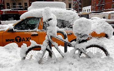 A bicycle and a taxi are covered in snow on the upper east side of New York city, January 27, 2011. A heavy snow blanketed the northeastern U.S. Thursday cancelling flights and making travel hazardous. REUTERS/Mike Segar
