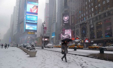A woman carries an umbrella as she walks through Times Square as snow falls in New York City, January 26, 2011. REUTERS/Gary Hershorn