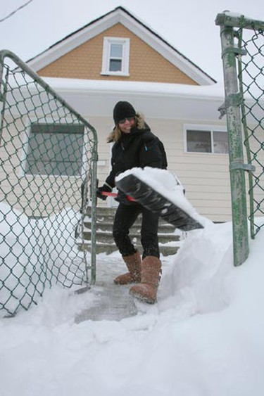 Jackie Fawcett clears the snow in front of her West End home in Winnipeg, Man. early Monday, Jan. 17, 2011, after 10 cm. of snow on the weekend. (MARCEL CRETAIN/Winnipeg Sun)