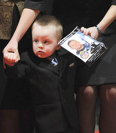 Christine Russell holds her son Nolan during funeral services for her husband, Toronto Police Sgt. Ryan Russell, in Toronto January 18, 2011. (Nathan Denette/POOL PHOTO/QMI Agency)