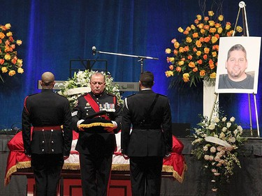 A Toronto police officer takes the cap of Police Sgt. Ryan Russell on the flag draped casket of Russell during his funeral services in Toronto January 18, 2011. (Nathan Denette/POOL PHOTO/QMI Agency)