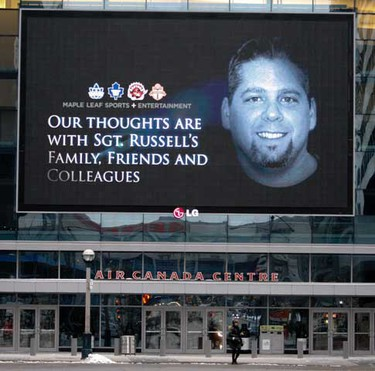 A police officer stands in front of a large electronic billboard on a downtown arena bearing condolences prior to funeral services for Toronto Police Sgt. Ryan Russell on January 18, 2011. (QMI AGENCY/Michael Peake)