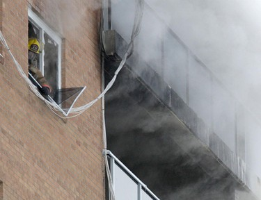 Smoke pours out of a suite at 1305 Taylor Ave in Winnipeg, where a fire broke out Saturday, Jan. 15. (C. PROCAYLO/Winnipeg Sun)