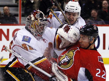 Ottawa Senators' Chris Kelly (22) crashes into Calgary Flames' goalie Henrik Karlsson (35) while defended by Anton Babchuk (33) during the third period of NHL action at Scotiabank Place in Ottawa Friday, January 14, 2011. Flames won 3-2. (Darren Brown/Ottawa Sun)