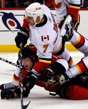 Calgary Flames' Adam Pardy (7) falls on Ottawa Senators' Jesse Winchester (18) during the third period of NHL action at Scotiabank Place in Ottawa Friday, January 14, 2011. Flames won 3-2. (Darren Brown/Ottawa Sun)