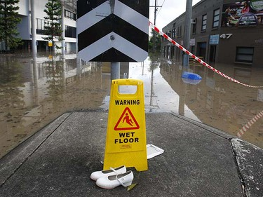 A sign and a pair of children's shoes are seen in front of a flooded street in the Brisbane suburb of Milton January 12, 2011. Thousands of residents of Australia's third-largest city evacuated homes on Wednesday as massive floods began to inundate the financial district, sparked panic buying of food and left authorities despairing for nearly 70 people missing. REUTERS/Mick Tsikas