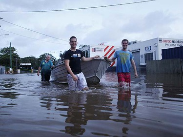 Local business owners walk their boat down a street in a commercial area of Brisbane January 12, 2011.     REUTERS/Tim Wimborne