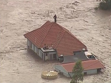 People are seen on the rooftop of a house in Grantham, a township between Toowomba and Brisbane, in this still image taken from video January 10, 2011. Tsunami-like flash floods raced towards Australia's third-largest city of Brisbane on Tuesday, prompting evacuations of its outskirts,  flood warnings for the financial district and predictions that  the death toll is likely to climb.   REUTERS/Nine Network via Reuters TV