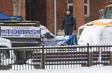 A police office inspects the crime scene on Toronto's Keele St. (Dave Thomas/QMI Agency)