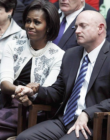 """U.S. first lady Michelle Obama holds the hand of Congresswoman Gabrielle Gifford's husband, NASA shuttle commander Mark Kelly, as they listen to President Barack Obama speak at the """"Together We Thrive: Tucson and America"""" event held to support and remember the victims of the mass shooting, at the University of Arizona in Tucson, Arizona, January 12, 2011. (Reuters)"""