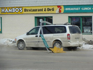 A vehicle slid through the intersection of Notre Dame Avenue and Flint Street Wednesday, Jan. 12, 2011, knocking a light standard onto the top of a parked van. No injuries were reported. Police took statements from the driver and the owner of the parked van. (SHELLEY COOK/For The Winnipeg Sun)
