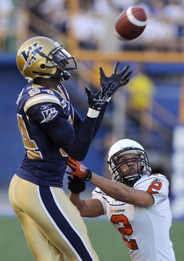 Winnipeg Blue Bombers Greg Carr (84) hauls in a pass in front of B.C. Lions Davis Sanchez (2) during overtime of Canadian Football League action in Winnipeg, Oct. 11, 2010. (Fred Greenslade/REUTERS)